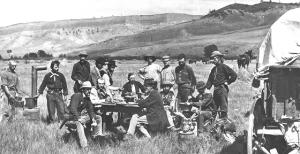 Comida en el campamento de Ferdinand V. Hayden (al fondo de la mesa, con traje oscuro) durante su campaña de 1870 en Wyoming para el Servicio Geológico de EE.UU. Foto de William H. Jackson (fuente: Wikipedia).